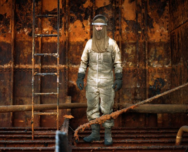 photograph of a steel worker inside a tanker